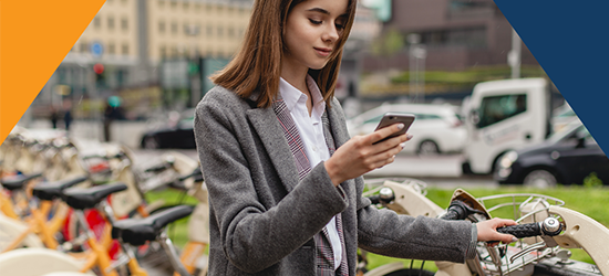 Woman looking at phone, choosing a bike image
